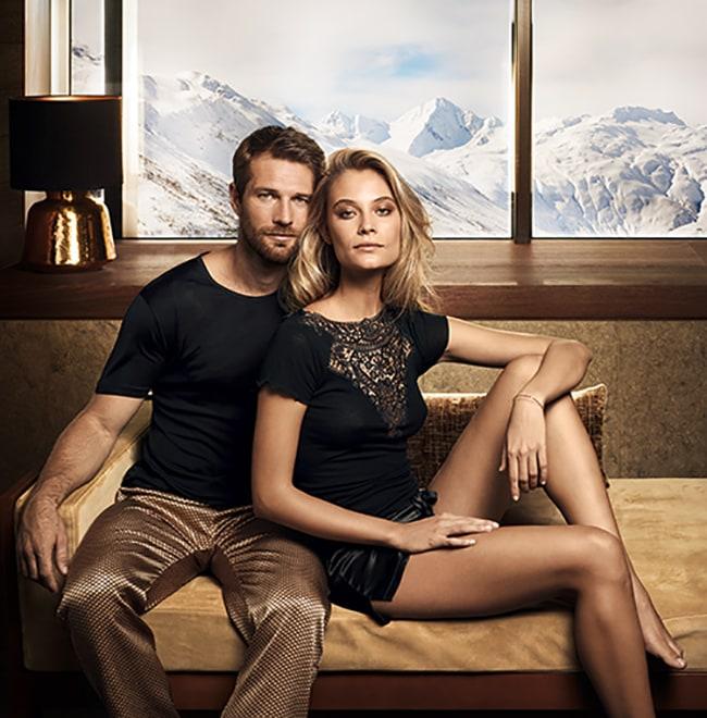 Mann und Frau gemeinsam auf der Couch in Nachtwäsche von Gute N8!